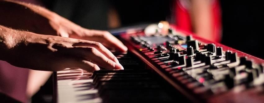 Twee handen die een stage piano aan het bespelen zijn