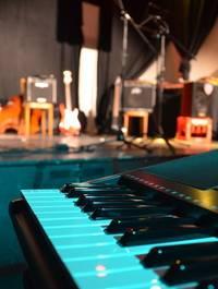 Een Roland stage piano die voor het podium staat