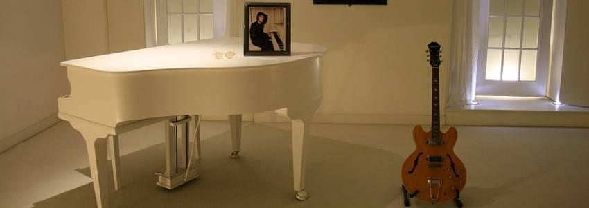 Een witte piano met een gitaar er naast