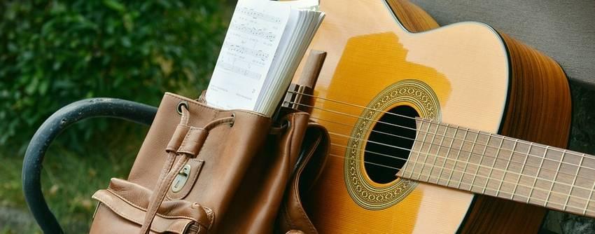 Een gitaar waar een schooltas voor staat met bladmuziek er in