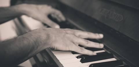 Twee handen die een piano aan het bespelen zijn