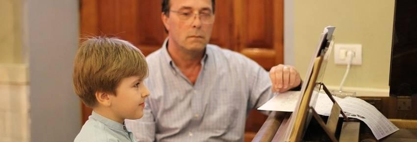 Een jongen die les krijgt van een pianoleraar
