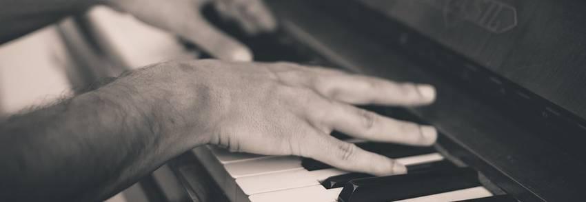 Twee handen die een piano bespelen