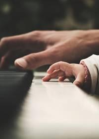 Een hand van een volwassene en een hand van een kind op een klavier