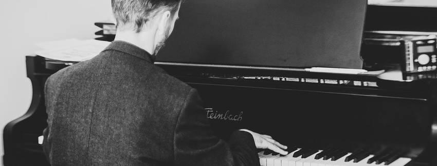 Een pianist die achter een piano zit