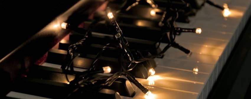 Kerstlichtjes die op het klavier van een piano liggen