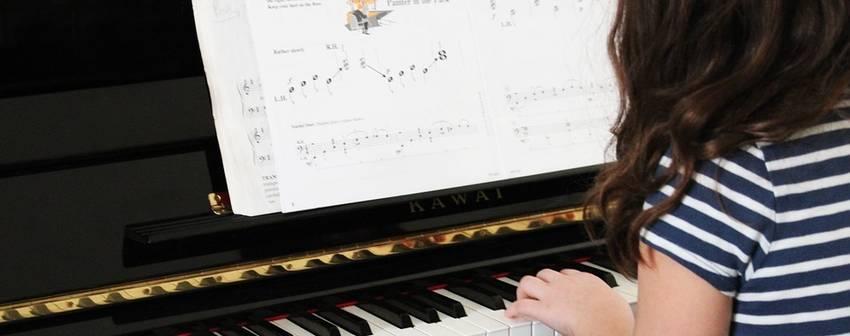 Een meisje dat achter ene piano aan het spelen is met een pianoboek